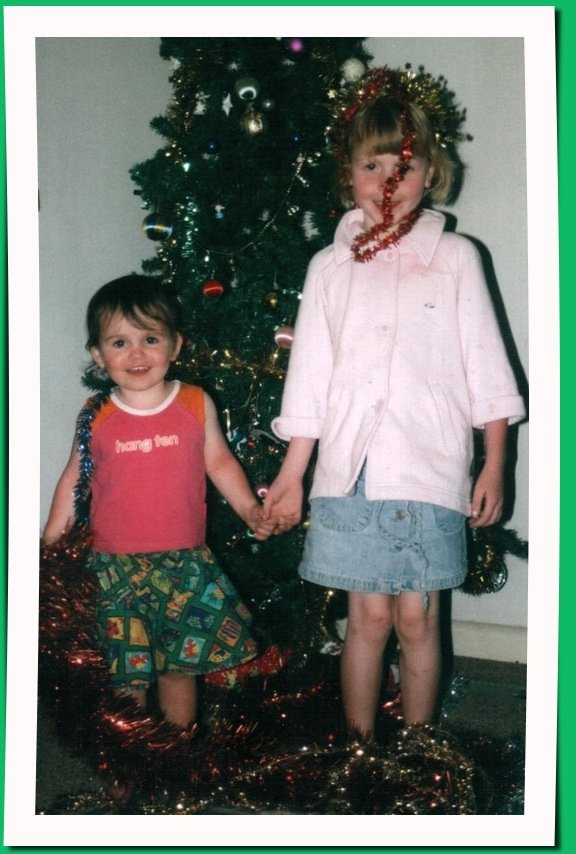 two young girls in front of a Christmas tree