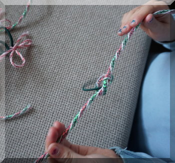 child tying string onto a hair tie