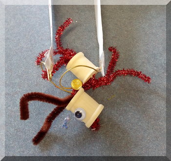 Cotton reel and pipe cleaner reindeer made by a child for Christmas