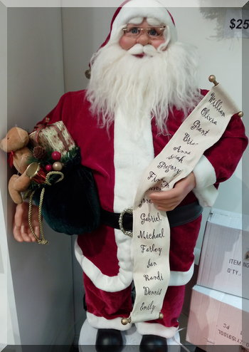 A model Santa holding a list of children's names