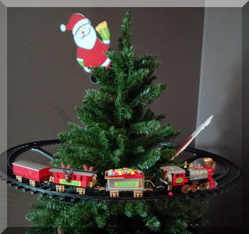 A Christmas train running around the top of a Christmas tree