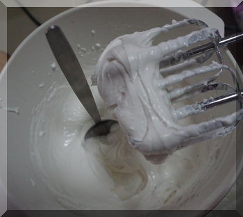 Spoon standing in icing to show how stiff the mixture is