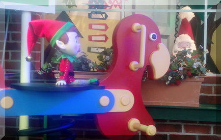Elf sitting on a colourful seesaw