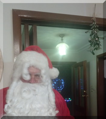 Santa standing under some mistletoe