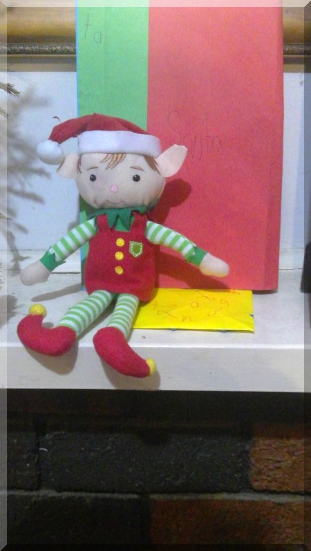 Elf in front of a colourful letter to Santa