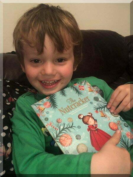 Smiling boy holding the Nutcracker book
