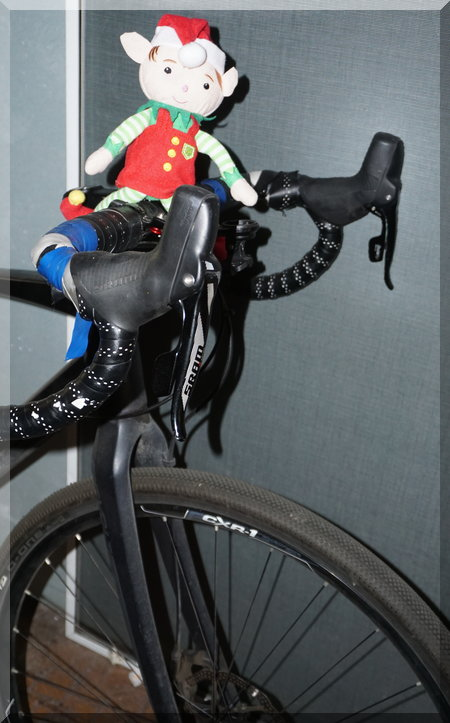 Tinkles the elf sitting on a full size bike