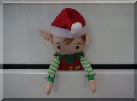 Tinkles the Elf peaking out of a white kitchen drawer