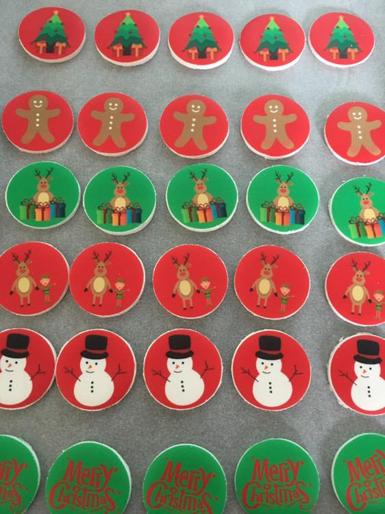 numerous cupcakes topped with a red or green Christmas topper
