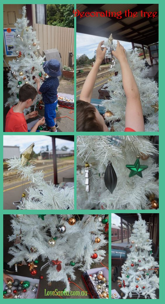 child decorated Christmas tree on the train station
