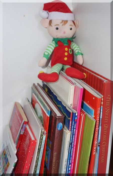 Tinkles the elf sitting on some Christmas books
