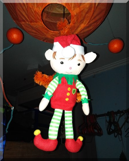 Tinkles the elf hanging from an orange ocotpod light fitting