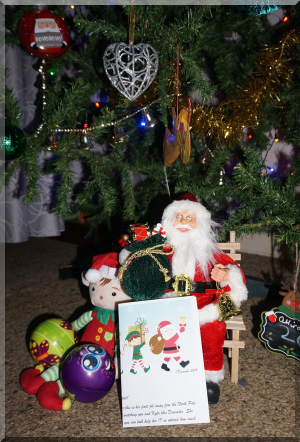 Tinkles the elf sitting by Santa under the Christmas tree
