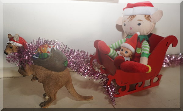 Christmas elf and baby elf is Santa;s sleigh pulled by a boomer