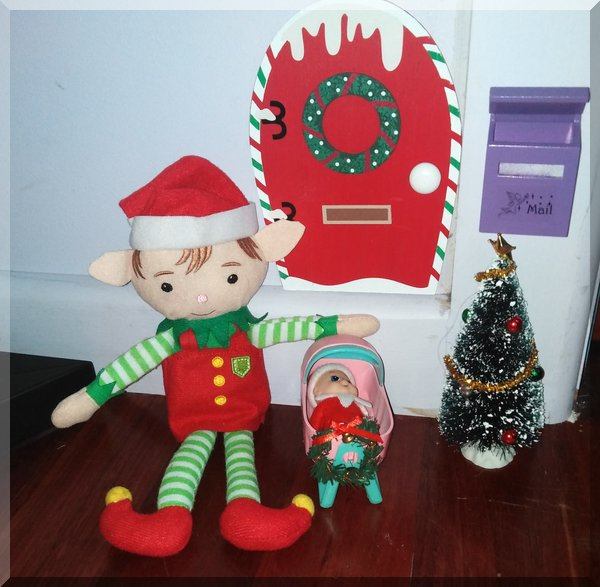 Christmas elf beside a Christmas tree and a baby elf in a pink cradle