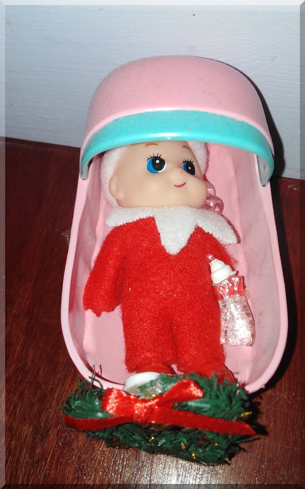 Baby Christmas elf in a cradle with a bottle and dummy
