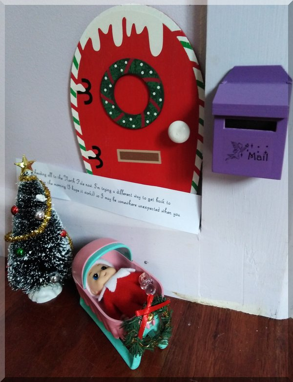 Baby elf in cradle beside a Christmas tree with a note from Tinkles