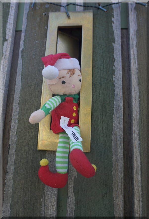 CHristmas elf hanging out of a letterbox