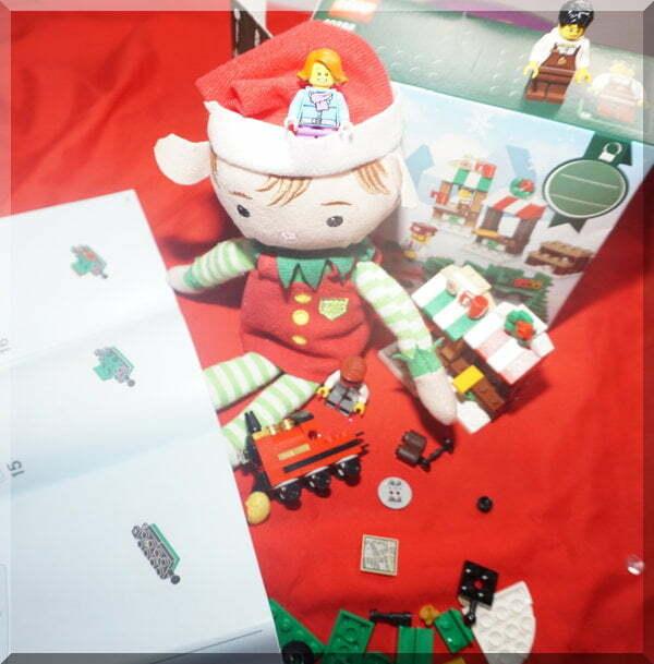 Christmas elf constructs a Lego train set