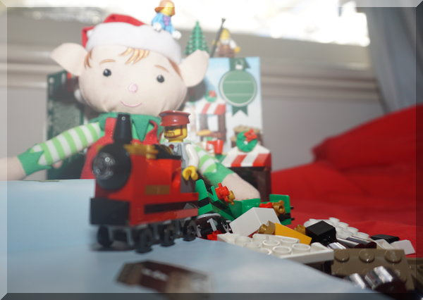 Tinkles the Christmas elf building a Lego train