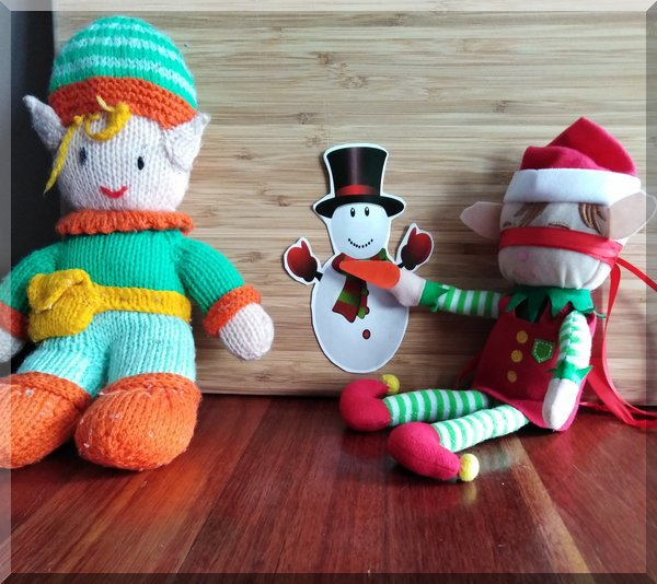 Christmas elf and tooth elf playing pin the nose on the snowman