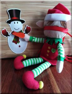 Christmas elf playing pin the nose on the snowman