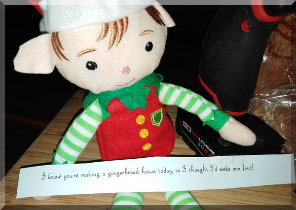 christmas elf holding a note about starting to build a gingerbread house