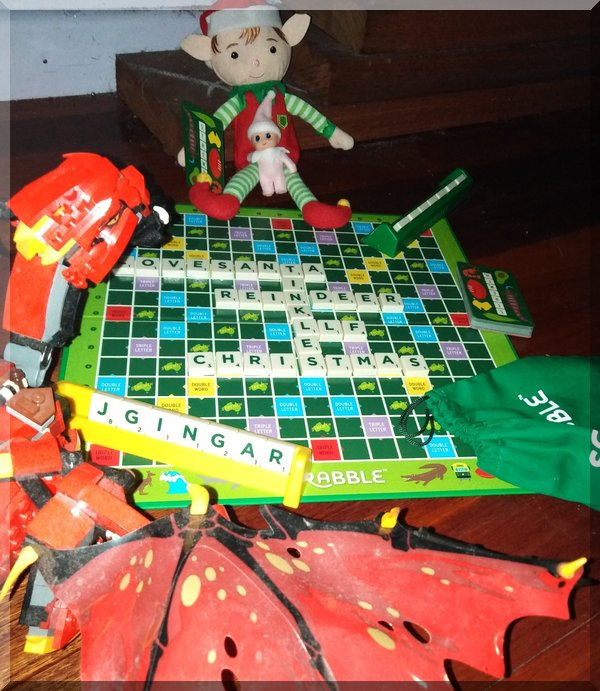 Lego Dragon and Christmas elf made Christmas words on the scrabble board