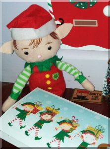 Tinkles sitting beside a doormat printed with 'Santa stop here!'