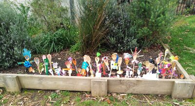 Collection of spoons decorated as people, standing up in a kinder garden bed