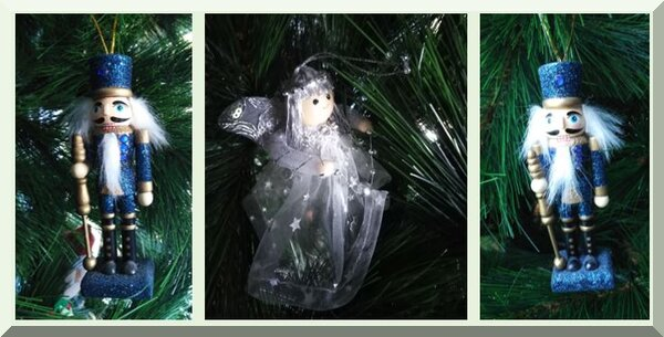 two blue nutcrackers and a white and silver angel hanging on a Christmas tree