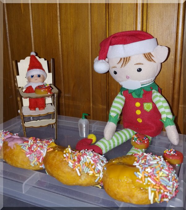 Christmas elves sitting with little and normal doughnuts