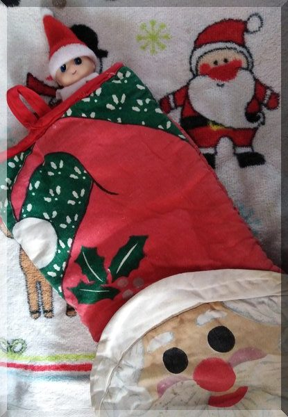 Baby Christmas elf tucked into a Santa over mitt