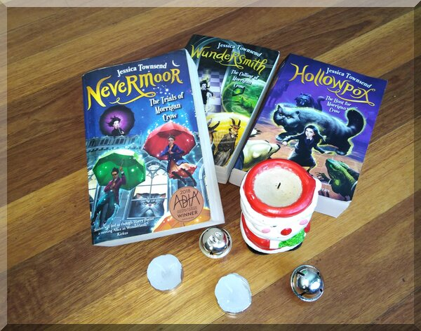 the first three books of the Nevermoor series beside a Santa candle