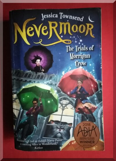 Nevermoor book cover showing people holding umbrellas in front of a large cat