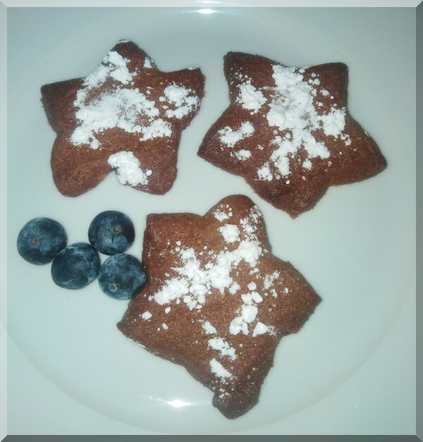 Icing sugar dusted pepparkakor on a plate with some blueberries