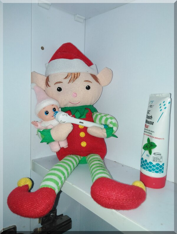 Christmas elf holding baby elf and a toothbrush to clean the baby's teeth