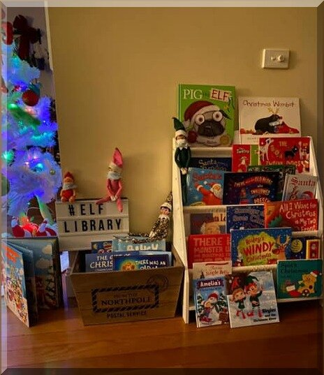 "Display of many CHristmas picture books and some elves with a sign ""Elf Library"""