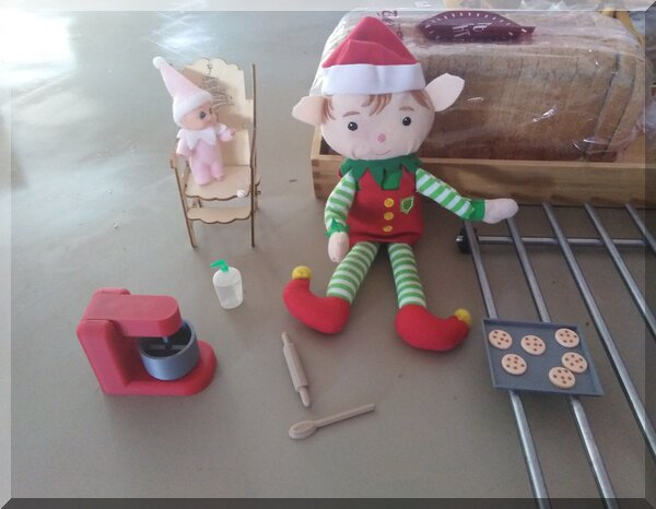 Christmas elf and baby elf beside a tray of biscuits