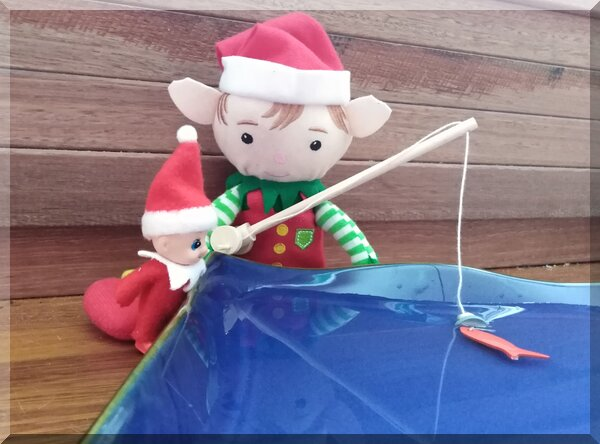 Christmas elves holding a fishing rod in front of a blue dish of water