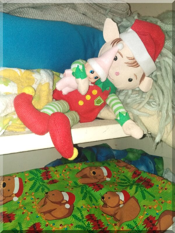 Christmas elves lying on blankets in a linen press