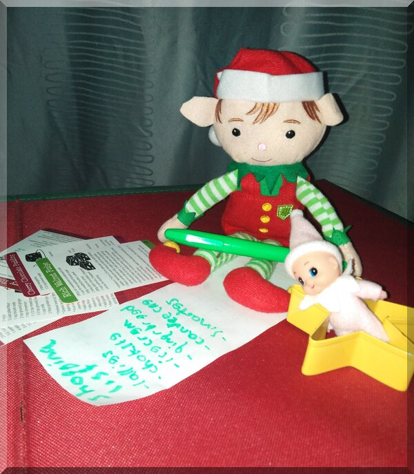 Christmas elf holding a green texta and writing a shopping list of sugary treats!