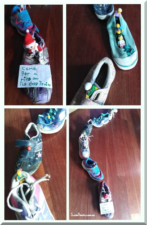 Christmas elf playing trains by sitting in a row of old shoes