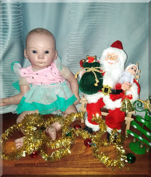 Santa sitting on bench holding a baby elf beside a doll