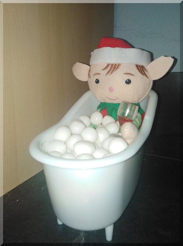 Christmas elf sitting in a bath with white balls as bubbles