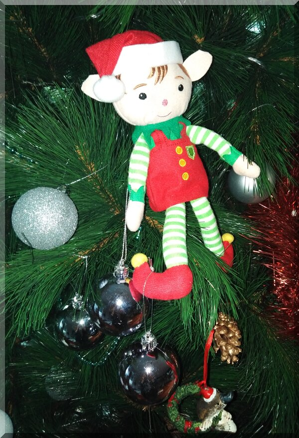 CHristmas elf holding two silver baubles and sitting in a Christmas tree