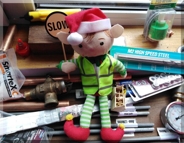 Christmas elf in a high vis vest holding a stop sign and sitting on various plumbing items