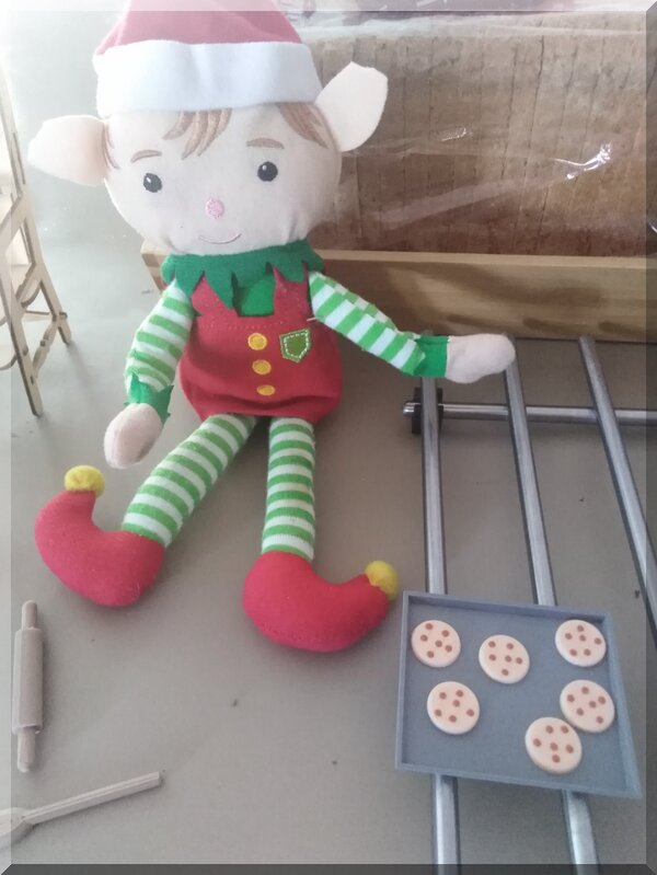 CHristmas elf sitting beside a tray of choc chip biscuits