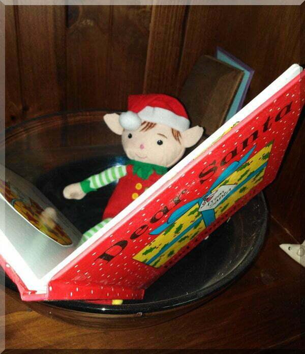 a CHristmas elf reading a picture book, Dear Santa