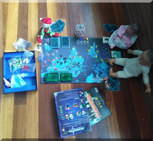 Christmas elf and angel playing the pandemic board game with some dolls on a wooden floor
